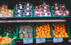Packaged and unpackaged fruit on supermarket shelves.