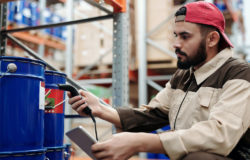 Man with a red cap and Notepad scans the label on a blue drum.