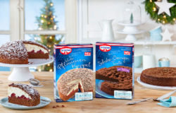 Oetker baking mixes: Winter Plum Cake and Chocolate Orange Tart. On a table next to a sliced tart and chocolate cake