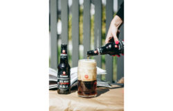 A woman's hand pours beer into a beer glass from a bottle A beer bottle stands on the table.