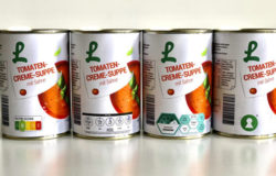 Four cans of tomato soup with different logos.