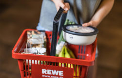 Red REWE shopping basket containing food and salad bowls from VYTAL held by a hand.