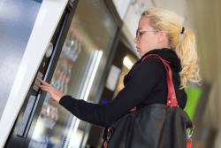 Convenience plays a major role for many consumers, especially in packaging. Photo: Casual Caucasian woman using a modern beverage vending machine. Her hand is placed on the dial pad and she is looking