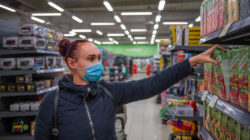 Woman wearing a blue mask reaches for packaged beverages on a supermarket shelf