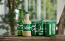 Old and new bottles in front of Carlsberg cans